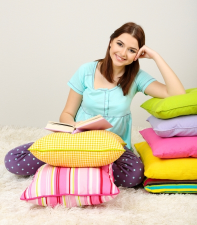 Beautiful young girl with pillows and book in room photo
