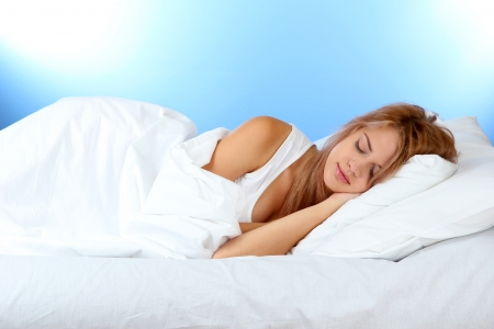 exersice: young beautiful woman sleeping on bed on blue background