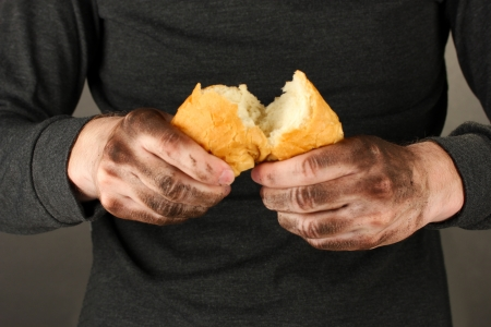 waif: homeless man holding a white bread, close-up