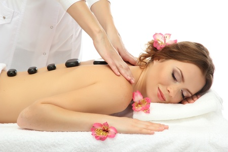beautiful young woman in spa salon getting massage with spa stones photo