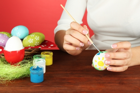 Young woman painting Easter eggs, on color background Stock Photo - 18890562