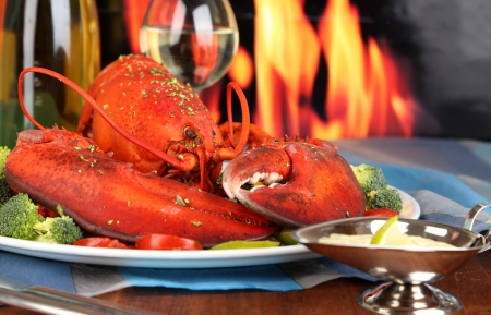 Red lobster on platter on wooden table on fire background photo