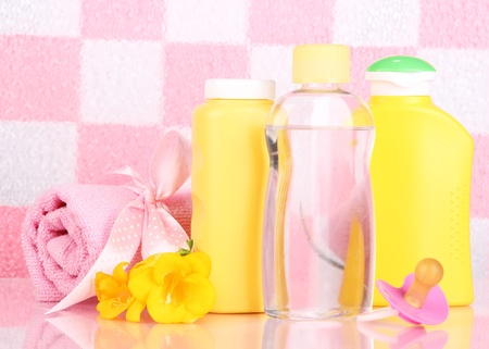 Baby cosmetics and towel in bathroom on pink tile wall background photo