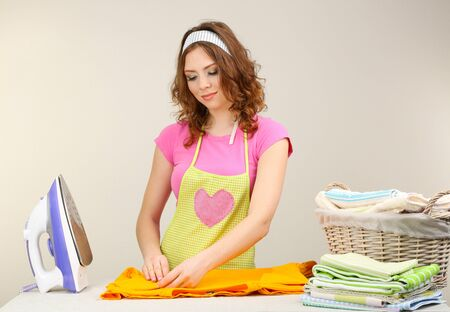 Young beautiful woman ironing clothes in room on grey background photo