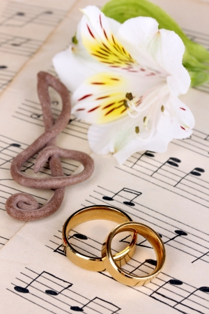 wedding vows: Treble clef, flower and wedding rings on musical background Stock Photo