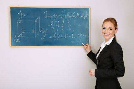Portrait of teacher woman writing on the chalkboard in classroom photo