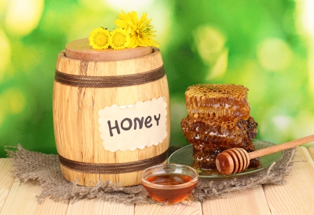 Barrel of honey and honeycomb on wooden table on on nature background photo