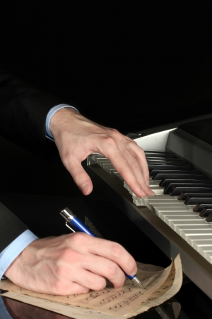 parer: man hands playing piano and writes on parer for notes