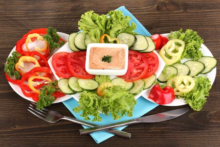 Chopped vegetables and sauce on plate on wooden table photo