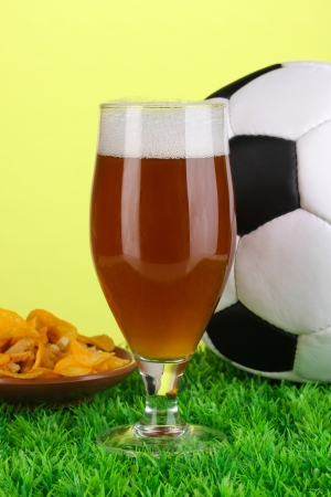 Glass of beer with soccer ball on grass on green background photo
