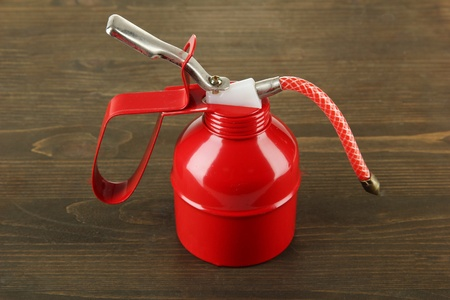 Red oil can, on wooden background Stock Photo - 18906794