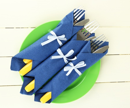 Forks and knives wrapped in blue paper napkins, on color wooden background Stock Photo - 18941105