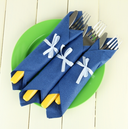 Forks and knives wrapped in blue paper napkins, on color wooden background Stock Photo - 18941051