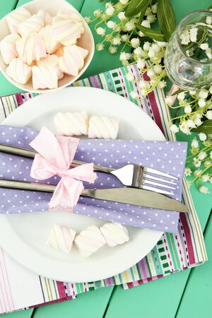 Table setting in violet and white tones on color wooden\ background