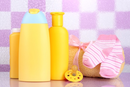 Baby cosmetics and towel in bathroom on violet tile wall background Stock Photo - 18941162