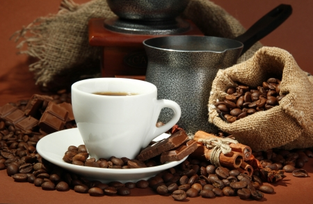 cup of coffee, grinder, turk and coffee beans on brown background photo