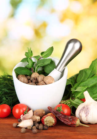 Composition of mortar,spices, tomatoes and  green herbs, on bright background photo
