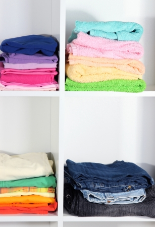 Clothes neatly folded on shelves photo