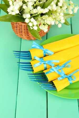 Blue plastic forks wrapped in yellow paper napkins, on color wooden background photo