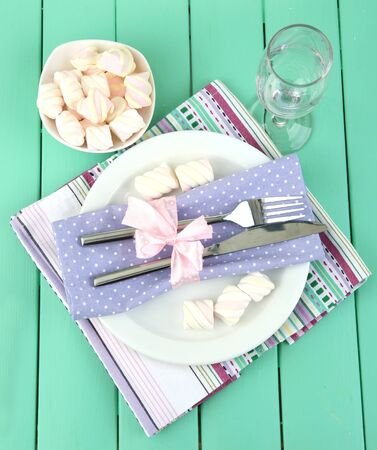 Table setting in violet and white tones on color  wooden background photo