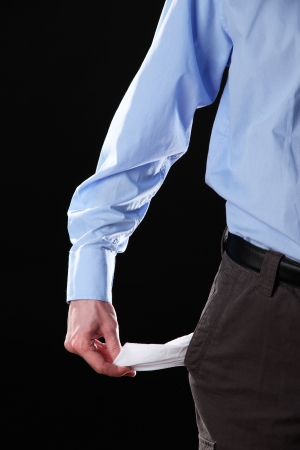 Business man showing his empty pocket, on black background photo