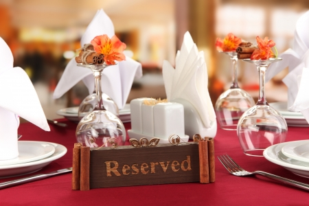 reserved: Reserved sign on restaurant table with empty dishes and glasses