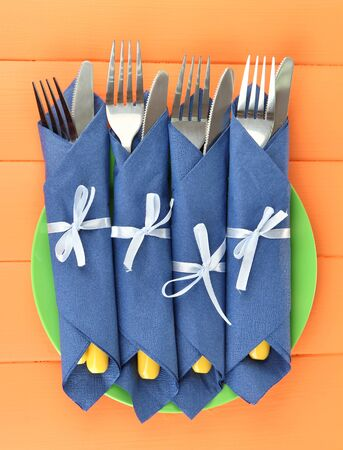 Forks and knives wrapped in blue paper napkins, on color wooden background Stock Photo - 19046972