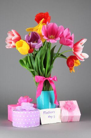Beautiful tulips in bouquet with gifts and note on gray background photo
