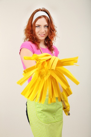 Young housewife with mop on grey background photo