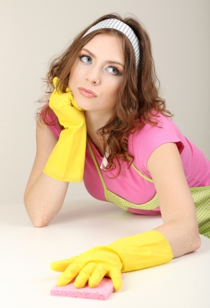 Young housewife cleaning up table at home on grey background photo