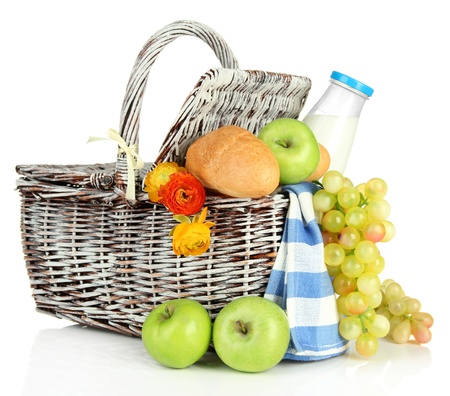 Picnic basket with fruits and bottle of milk, isolated on white photo