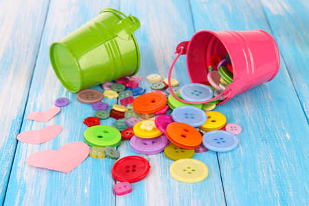 Colorful buttons strewn from buckets on wooden background photo