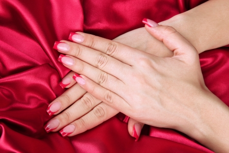 Female hands on color fabric background photo