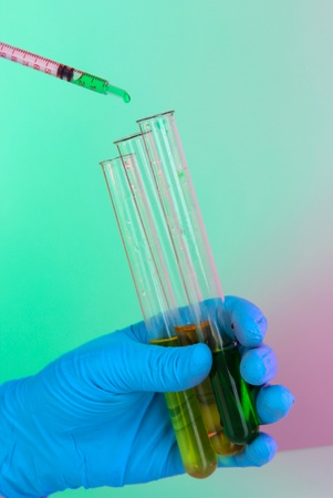Hands in gloves and test tubes on blue-purple background photo