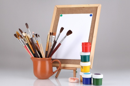 Small easel with sheet of paper and art supplies isolated on white photo
