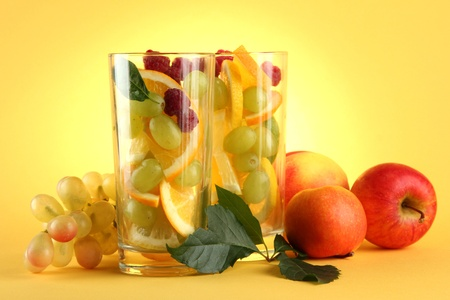 transparent glasses with citrus fruits, on yellow background photo