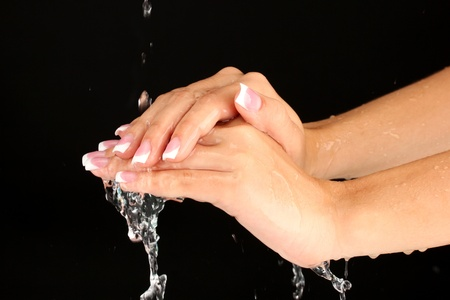 Washing womans hands on black background close-up photo