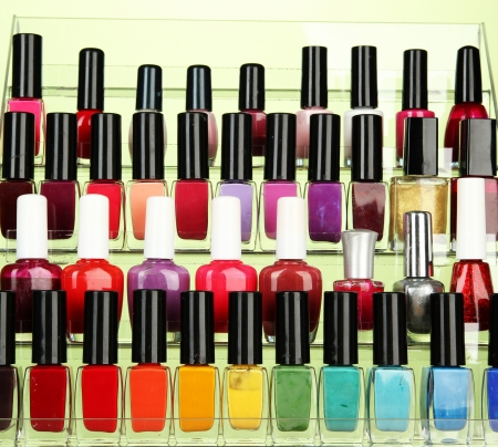 Bright nail polishes on shelf on green background photo