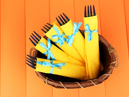 Blue plastic forks wrapped in yellow paper napkins, in wicker basket, on color wooden background photo