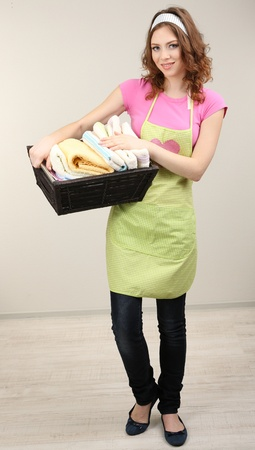 laundry room: Housewife carrying laundry basket full of clothing in room on grey background