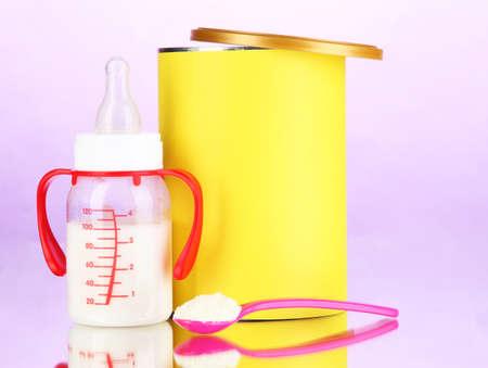 fondo para bebe: Botella con la leche y los alimentos para beb�s en el fondo p�rpura Foto de archivo