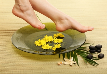woman foot: Female feet in spa bowl with water, on bamboo mat