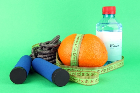 Orange with measuring tape,skipping rope and bottle of water, on color background photo