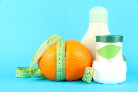 Orange with measuring tape and body cream, on color background photo