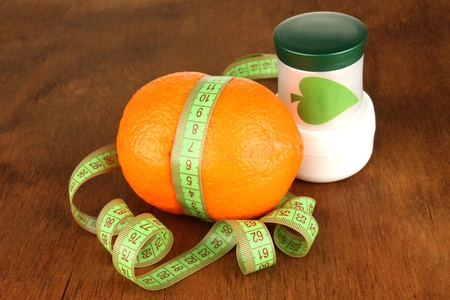 Orange with measuring tape and body cream, on wooden background photo
