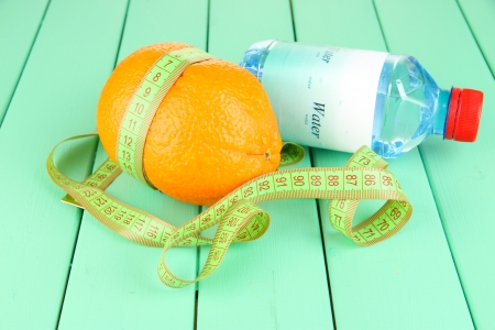 Orange with measuring tape, bottle of water, on wooden background photo