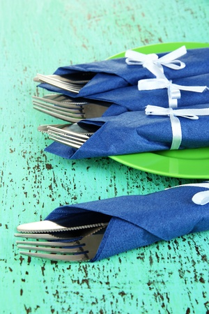 Forks and knives wrapped in blue paper napkins, on color wooden background photo