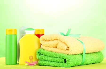 Baby cosmetics and towels on wooden table, on green background photo