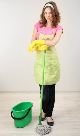 Young housewife with mop in room on grey background photo