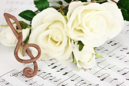 sheetmusic: Treble clef and roses on musical background Stock Photo